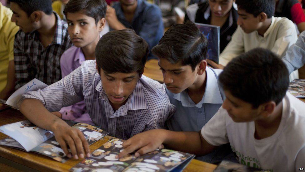 Pakistani boys study a comic book
