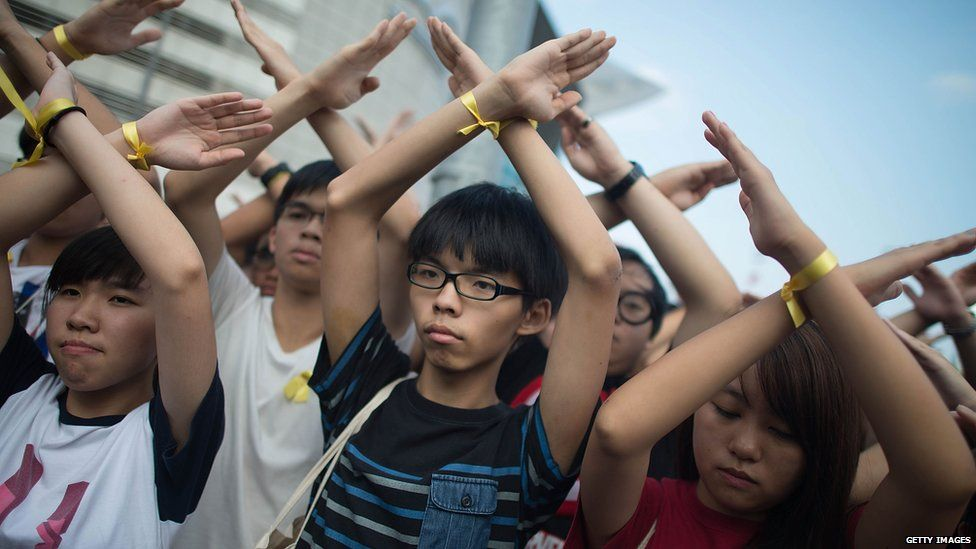 Student pro-democracy group Scholarism convenor Joshua Wong (C) makes a gesture at the Flag Raising Ceremony at Golden Bauhinia Square on 1 October 2014 in Hong Kong.