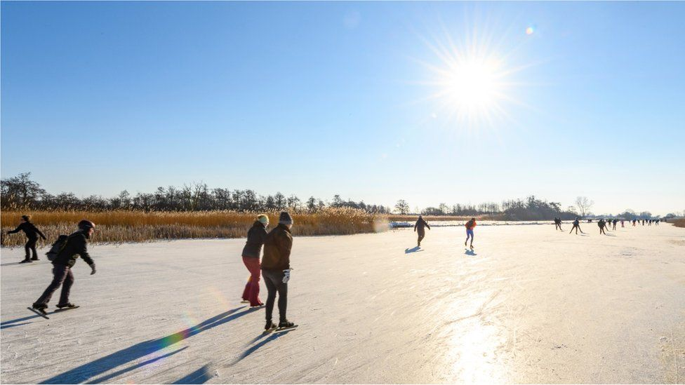 People ice skating on a frozen canal in the Weerribben-Wieden nature reserve in Overijssel during a cold winter day in The Netherlands on February 12, 2021 in Belt-Schutsloot, Netherlands.