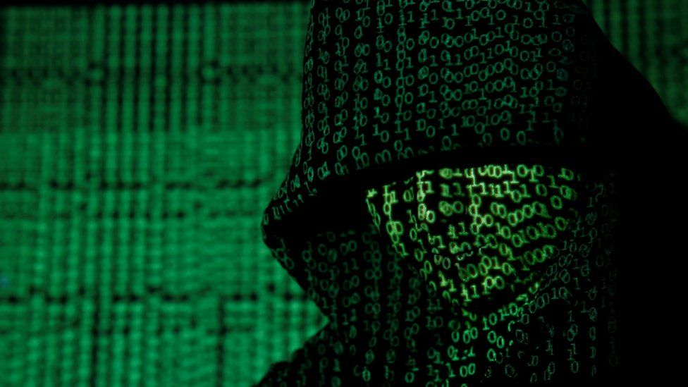 Hooded man with green code projected overtop