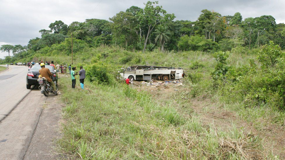 A vehicle involved in an accident lies on its in a wooded area along a highway in Cameroon.