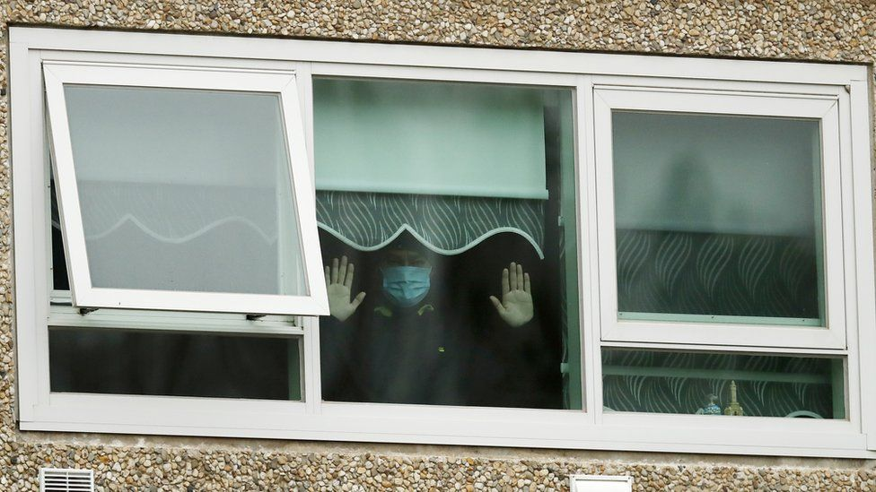 A man wearing a mask holds his hands up to the window in one of the housing towers