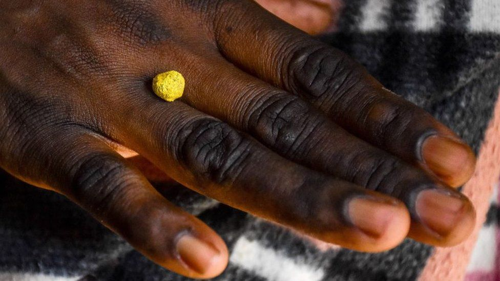 A woman holds raw gold on her hand at a mine