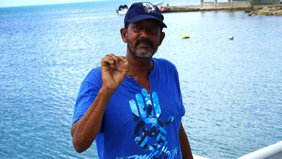 Devon Warner stands by the ocean in Barbuda