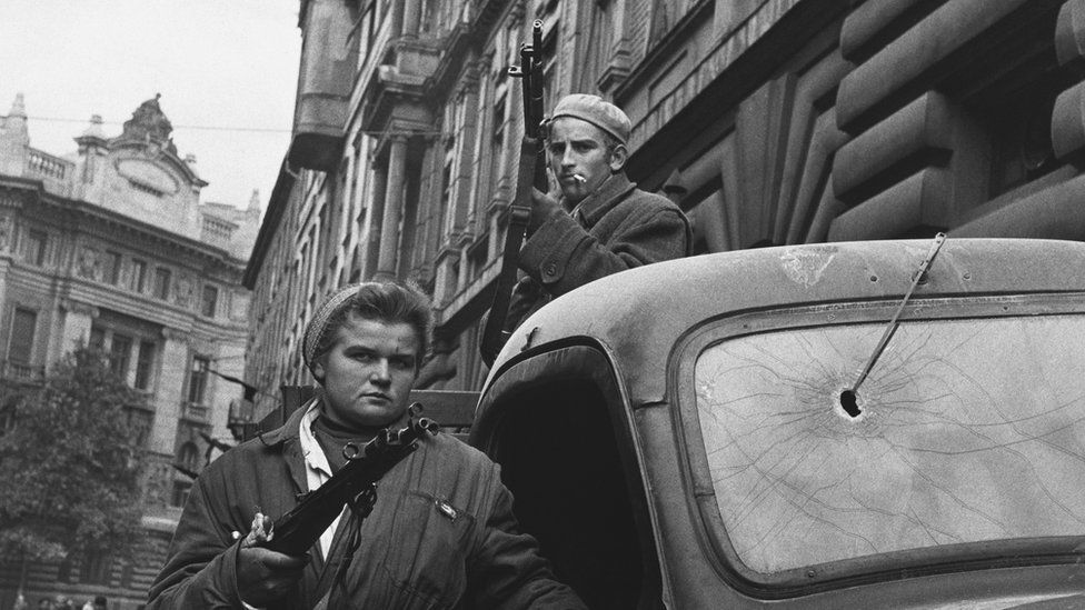 Two Hungarian freedom fighters stand armed by a truck in Budapest during the Hungarian Revolution of 1956.