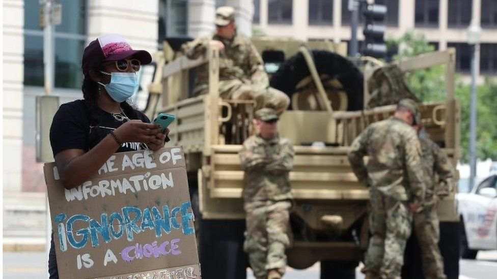 National Guardsmen watch on as a protester demonstrates in Washington DC