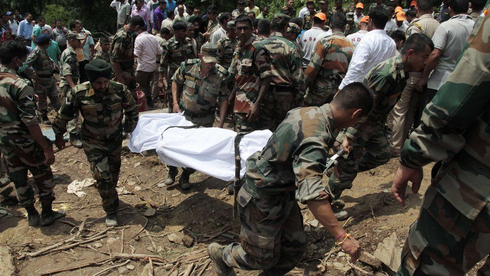 Indian army soldiers and rescue personnel look for survivors after a landslide along a highway at Kotrupi