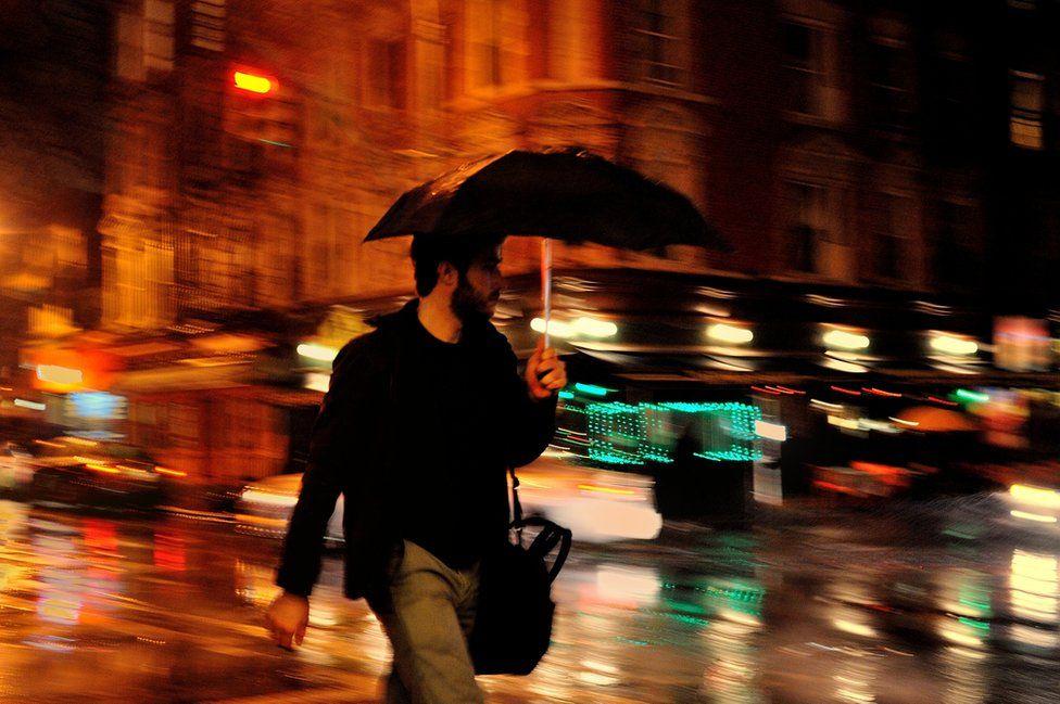 A man walks in the rain with his umbrella