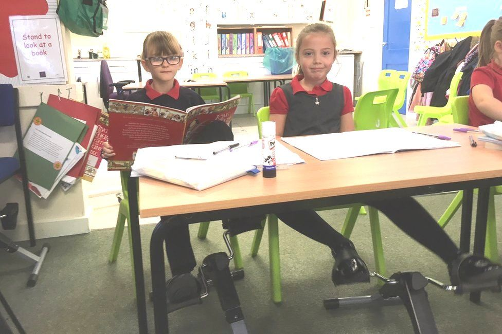 Pupils using pedal machines under their desks at school