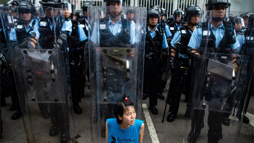 A protester sits in front of riot police outside Legislative Council in Hong Kong