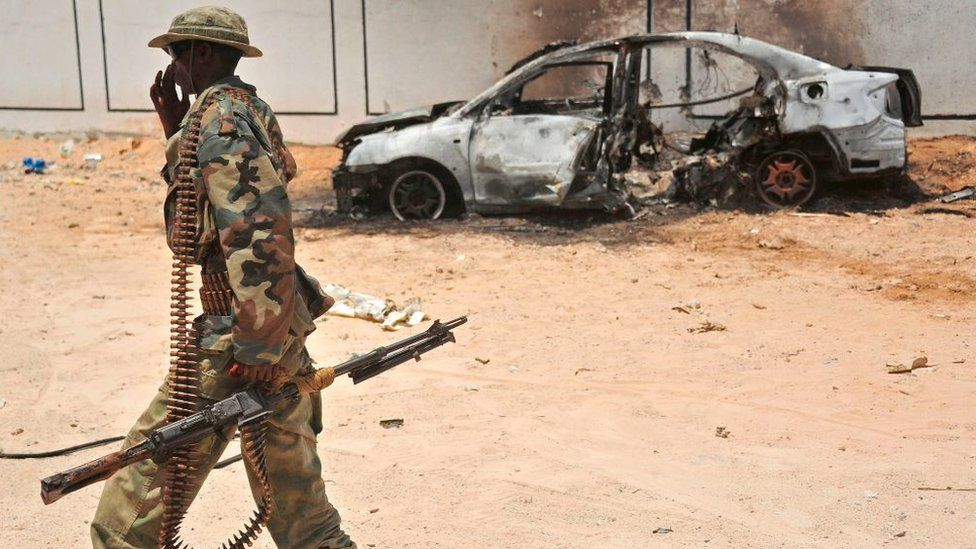 A Somali soldier patrols next to the burnt-out wreckage of a car that was used by suspected al-shabab fighters on April 16, 2017.