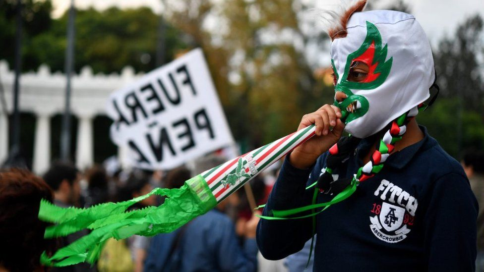 A boy in a mask watches the demonstration in Mexico City
