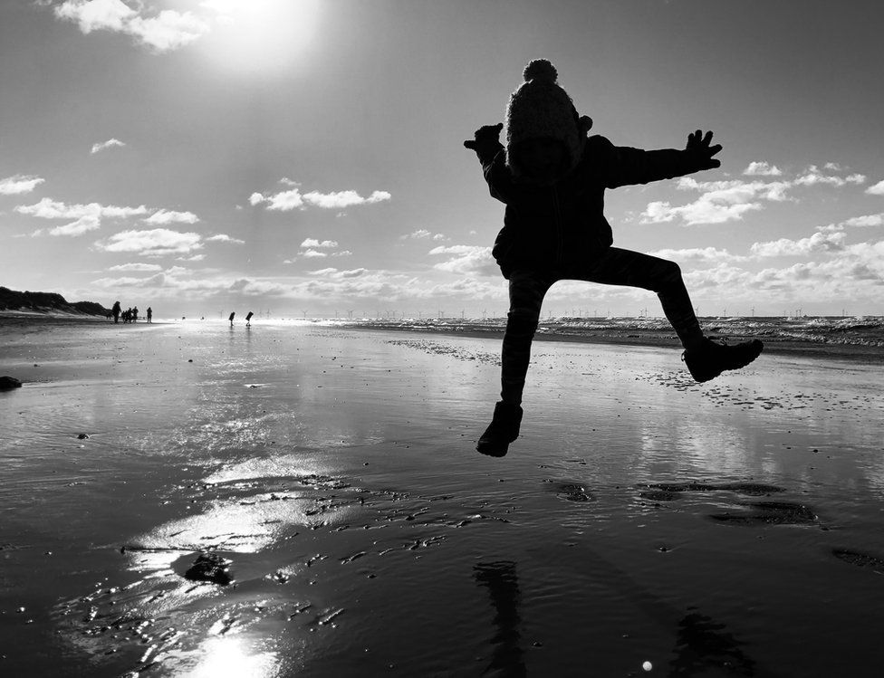 The silhouette of a girl jumping on a beach