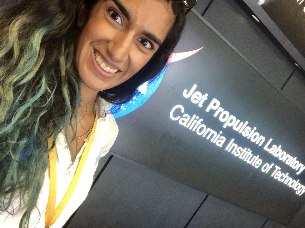 A woman with dark brown and green hair stands in front of a sign reading 'Jet Propulsion Laboratory, California Institute of Technology