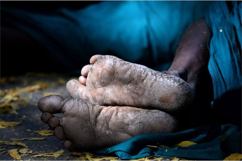 A shaft of light catches the weathered feet of an Indian farmer from the southern state of Tamil Nadu, as he sleeps on a foothpath during a protest in New Delhi on March 26, 2017.