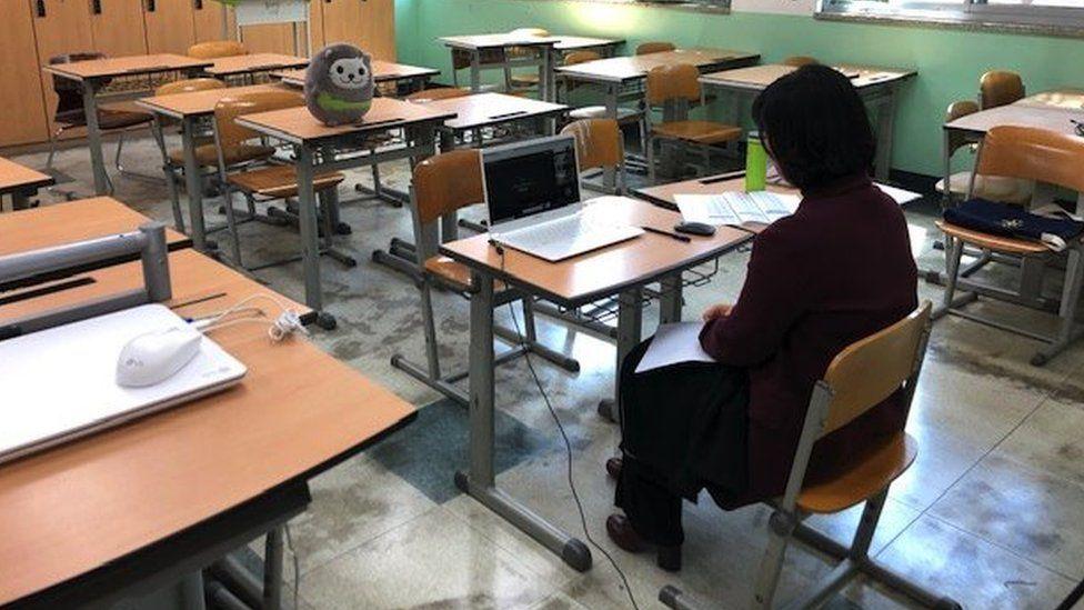 A teacher sits in an empty classroom