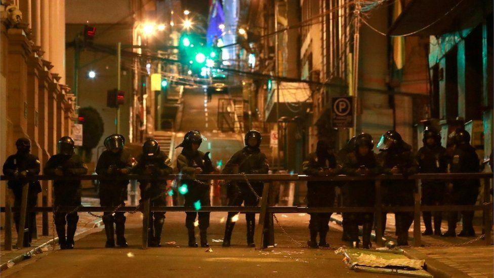 Riot police blocking off a street in La Paz