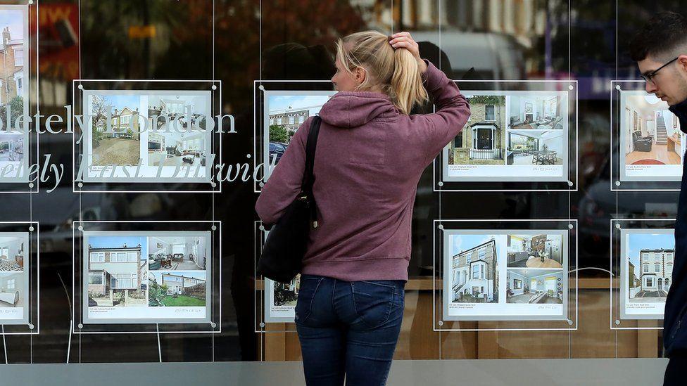 A woman looks in an estate agent's window in London