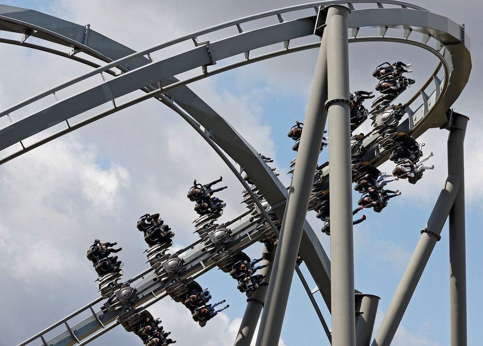 People ride the Swarm rollercoaster