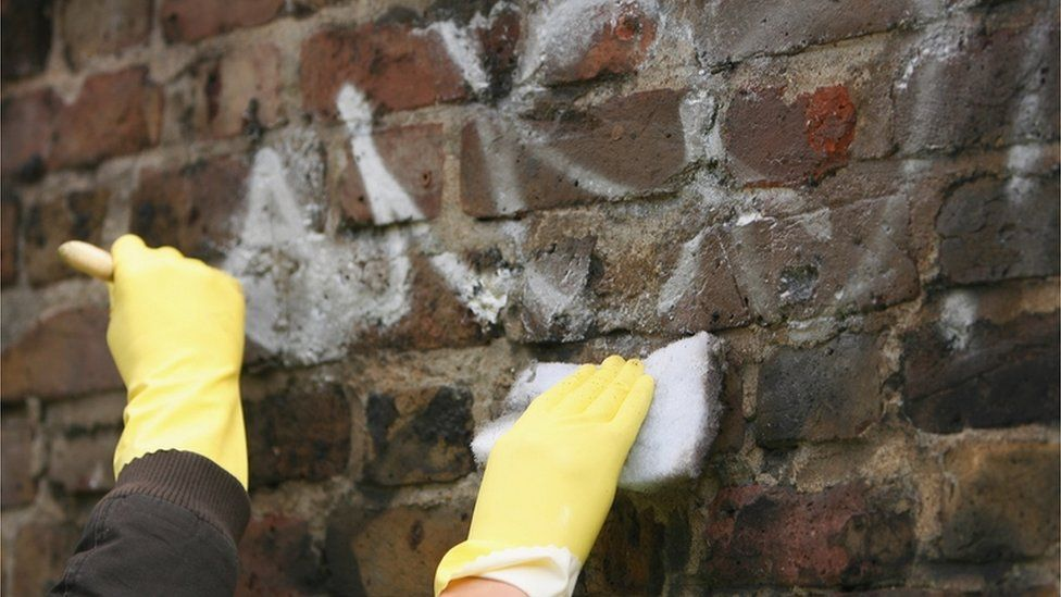 Graffiti being removed from a wall