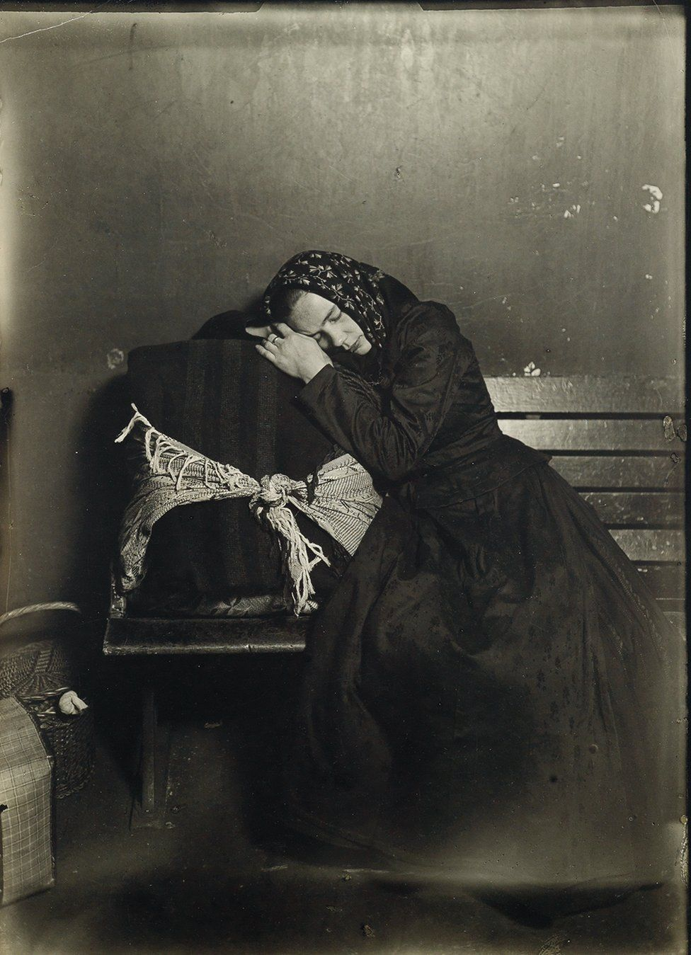 An immigrant sleeps on her case.