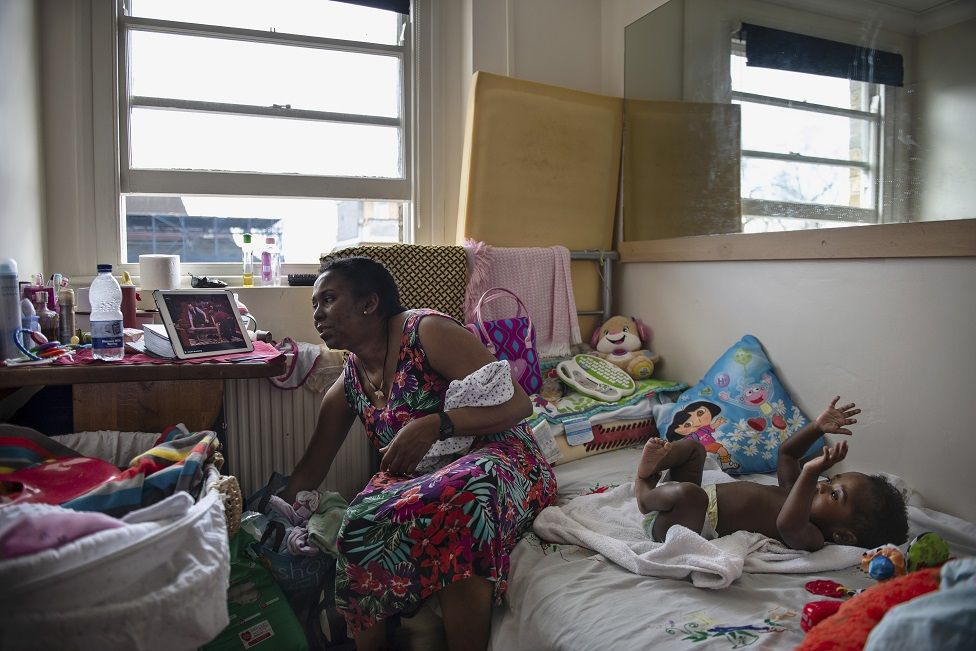 A mother and her child sit in a cluttered room