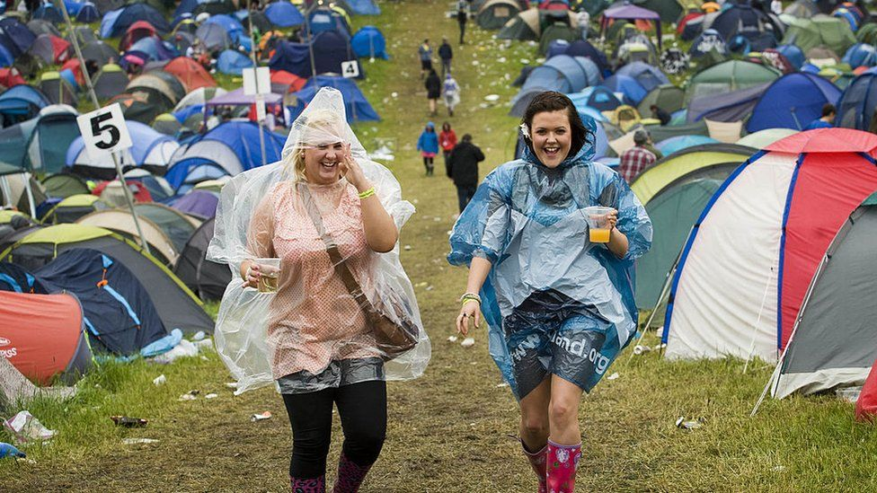 Women with ponchos on at a festival