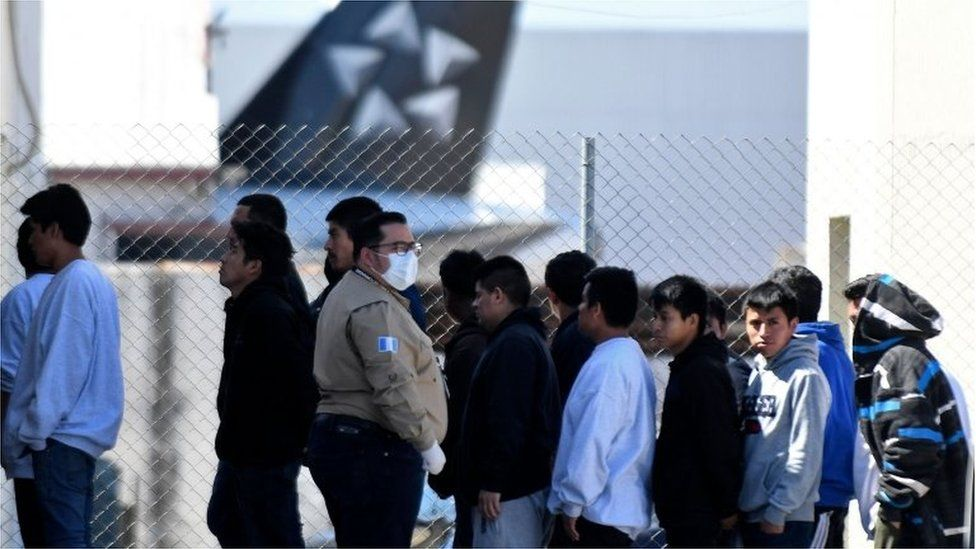 Deportees queue at an air force base in Guatemala on 12 March
