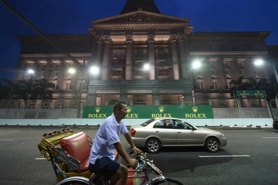 Commuters drive rides in front the museum gallery in Singapore on 15 September 2015, where the Formula One racing tournament will be held from 18-20 September 2015.