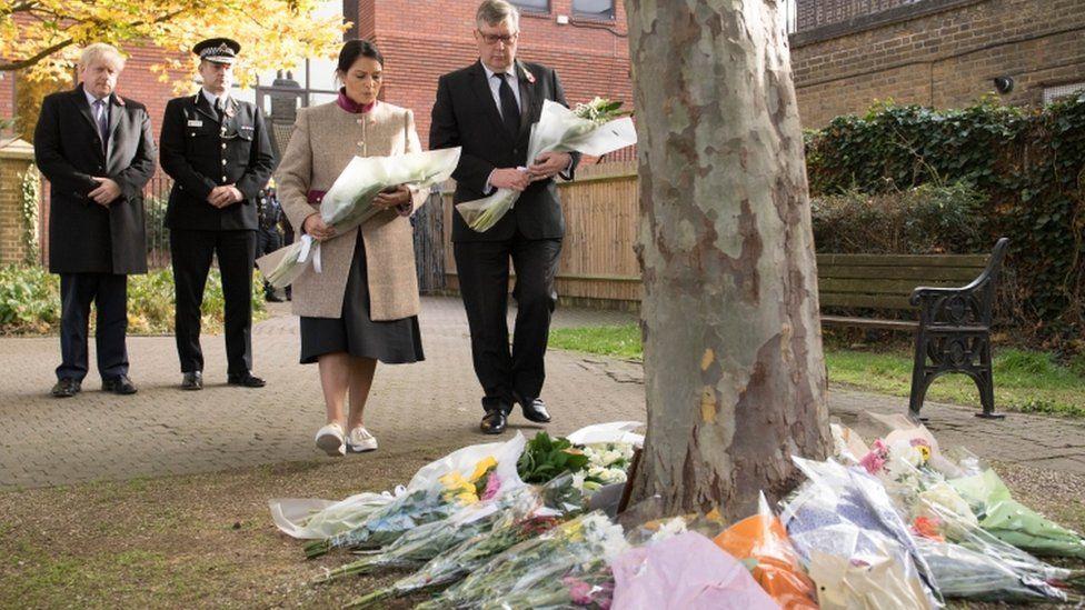 Priti Patel and Boris Johnson laying flowers