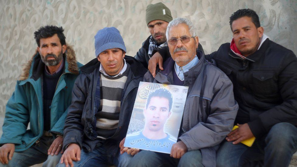 Othman Yahyaoui (C) poses with family members for a photo in the central Tunisian town of Kasserine on January 21, 2016, holding a portrait of his son, Ridha Yahyaoui