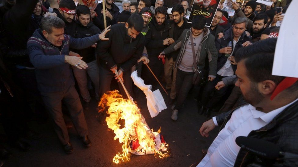 Protesters burn a UK and Israeli flag in Tehran