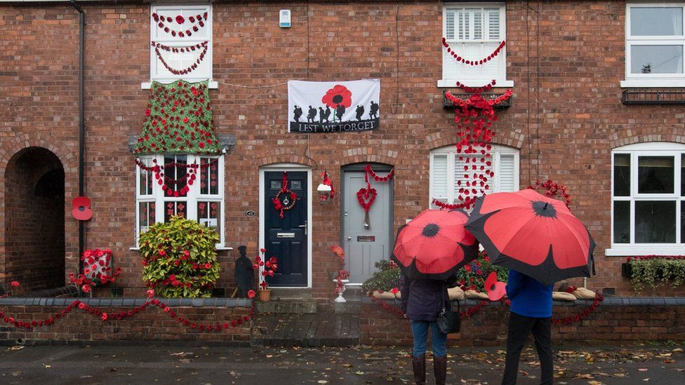 People look at a house in Station Road, Aldridge in Walsall which has transformed itself into Poppy Road as almost 100 houses have been decorated with 24,000 red poppies and silhouette statues of soldiers to honour local people who endured and lost their lives in the First World War.