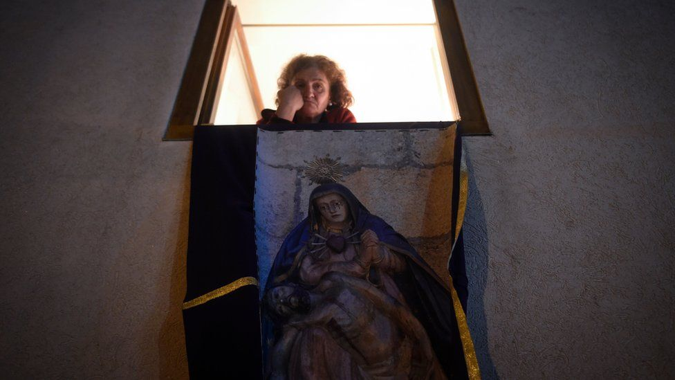 A woman looks out from her window, adorned with an imagery to celebrate Easter in Cambados, north-western Spain, on April 10, 2020, after religious processions were cancelled