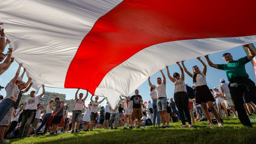 Belarusian people hold a giant historical flag of Belarus during a rally in support of the Belarusian opposition