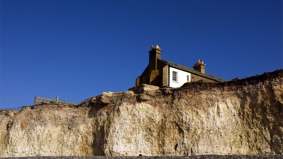 Row of cottages near an eroding cliff edge at Birling Gap and the Seven Sisters, East Sussex