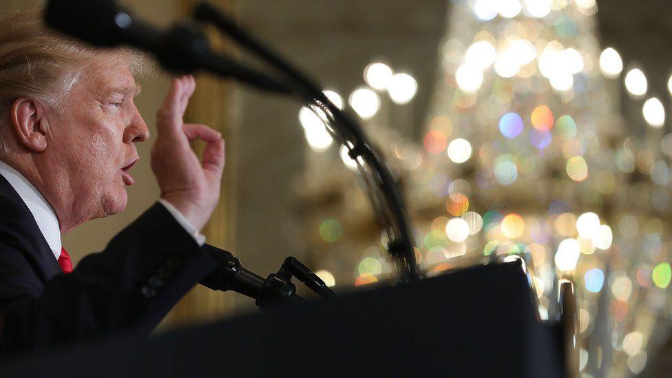 Donald Trump speaking at a podium