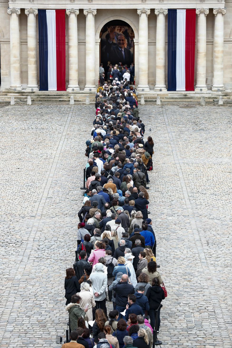 Visitors wait to view the coffin of former French President Jacques Chirac on 29 September 2019.