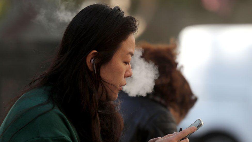 A pedestrian smokes an e-cigarette in San Francisco, 2019