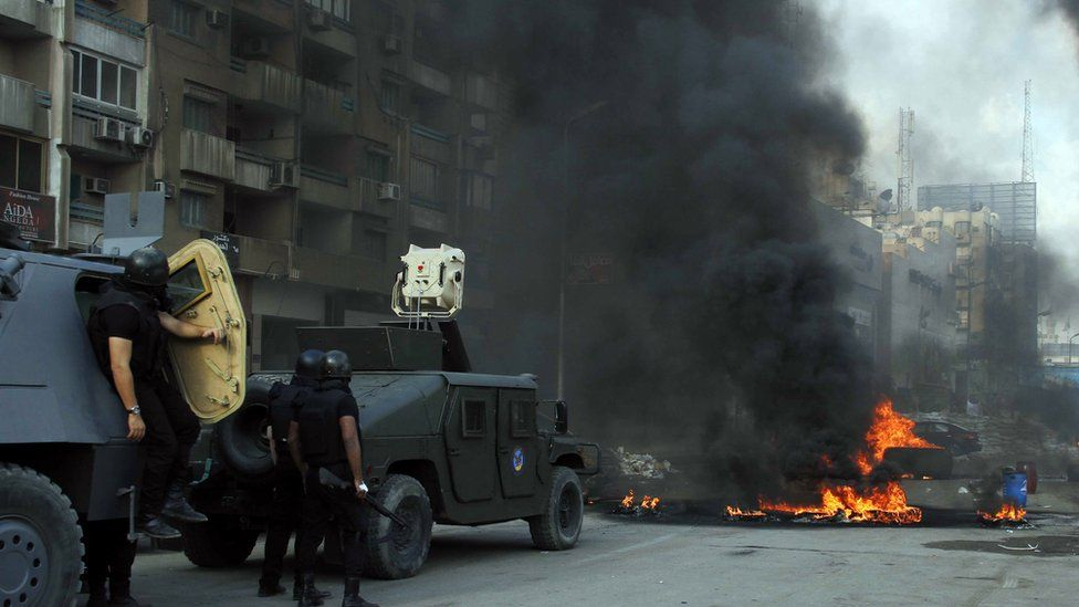 Armoured vehicles approach a flaming barrier in Cairo on 14 August 2013