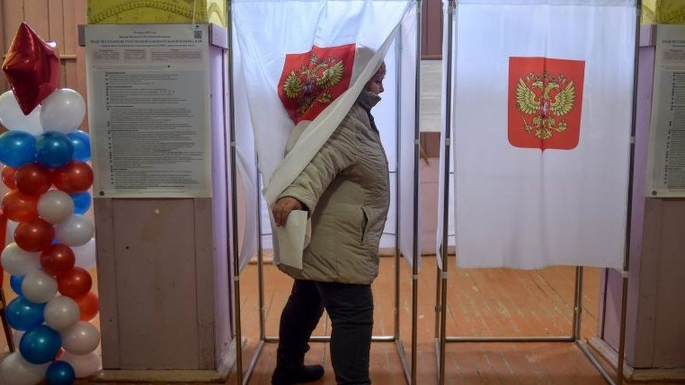 A woman comes out of a polling station