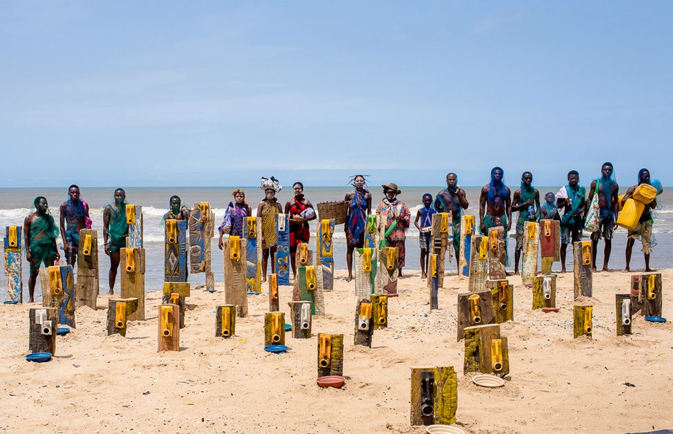 People standing near artwork using jerrycans by artist Serge Attukwei Clottey on a beach in Accra, Ghana