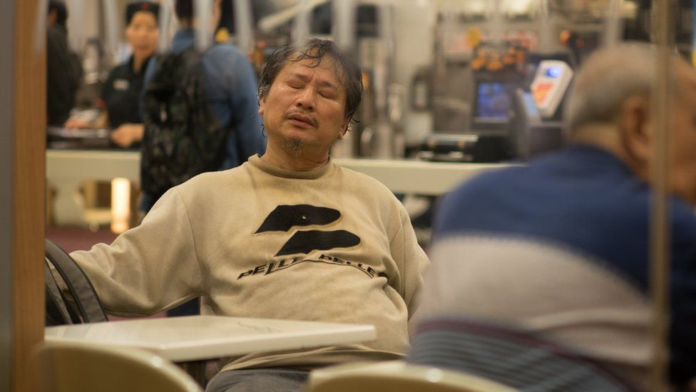 Mr Chan with his eyes closed in a chair