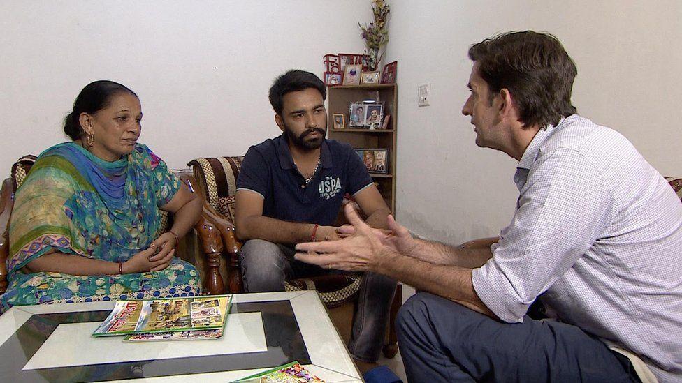 Correspondent Justin Rowlatt speaking with two of Singh's followers.