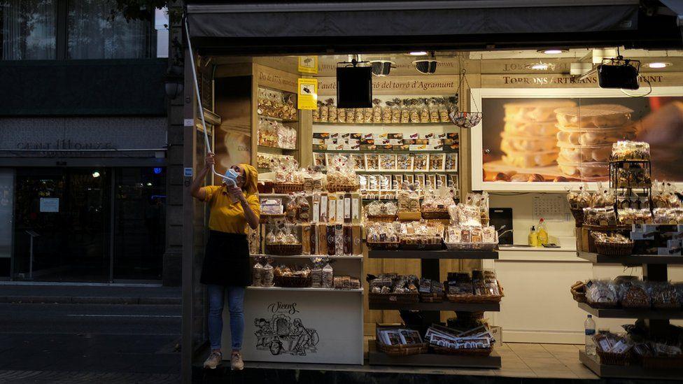 Shopkeeper closing up in La Rambla, Barcelona