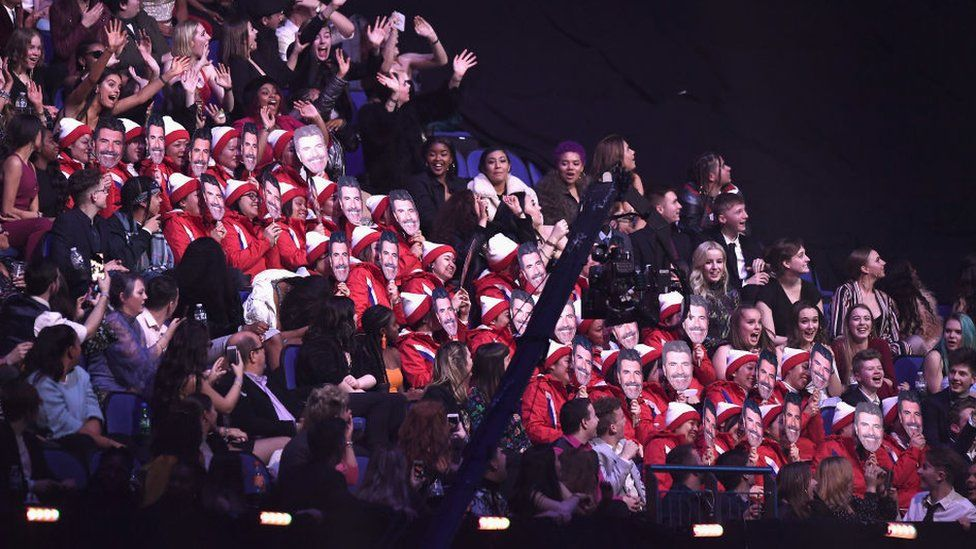 Members of the audience wearing Simon Cowell masks at The BRIT Awards