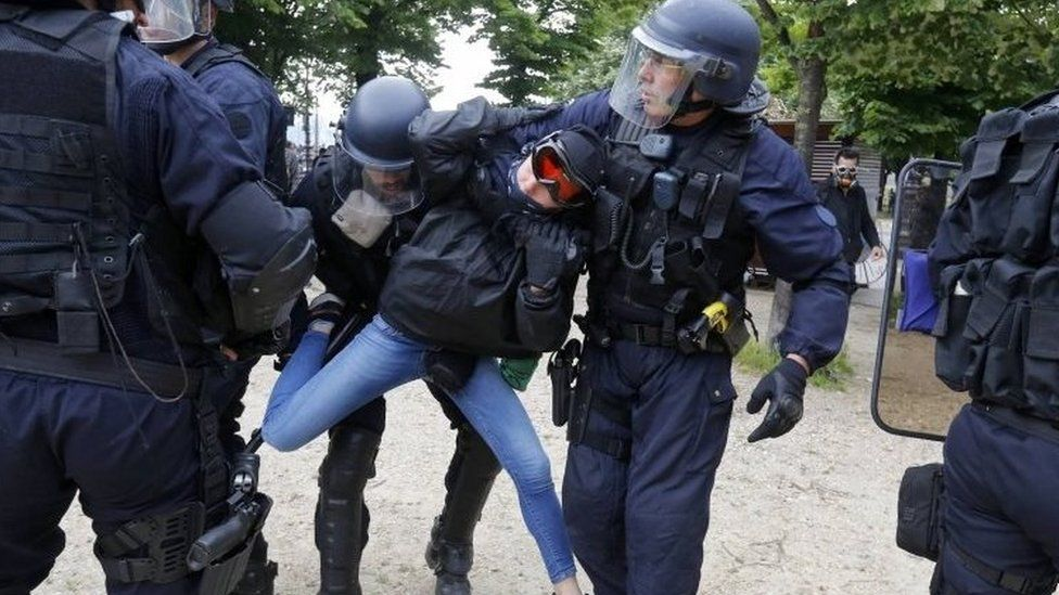 French CRS riot police apprehend a demonstrator during clashes at the Invalides square during a demonstration in Paris as part of nationwide protests against plans to reform French labour laws.