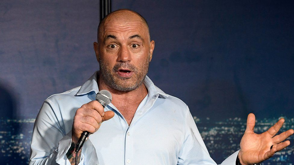 Joe Rogan performs at a comedy show, holding a mic and raising his eyebrows at the audience