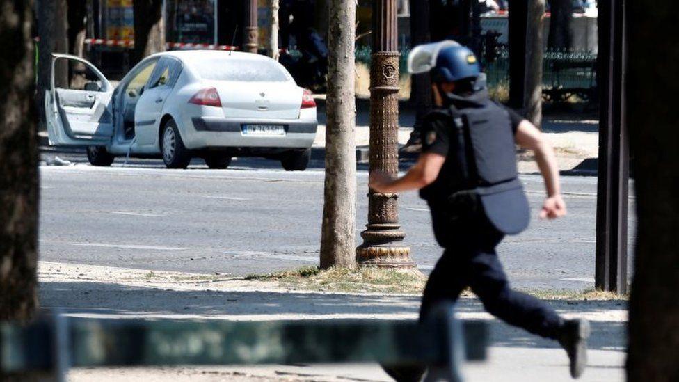 A French gendarme runs past a car on the Avenue des Champs-Élysées after an incident in Paris, France, on 19 June 2017.