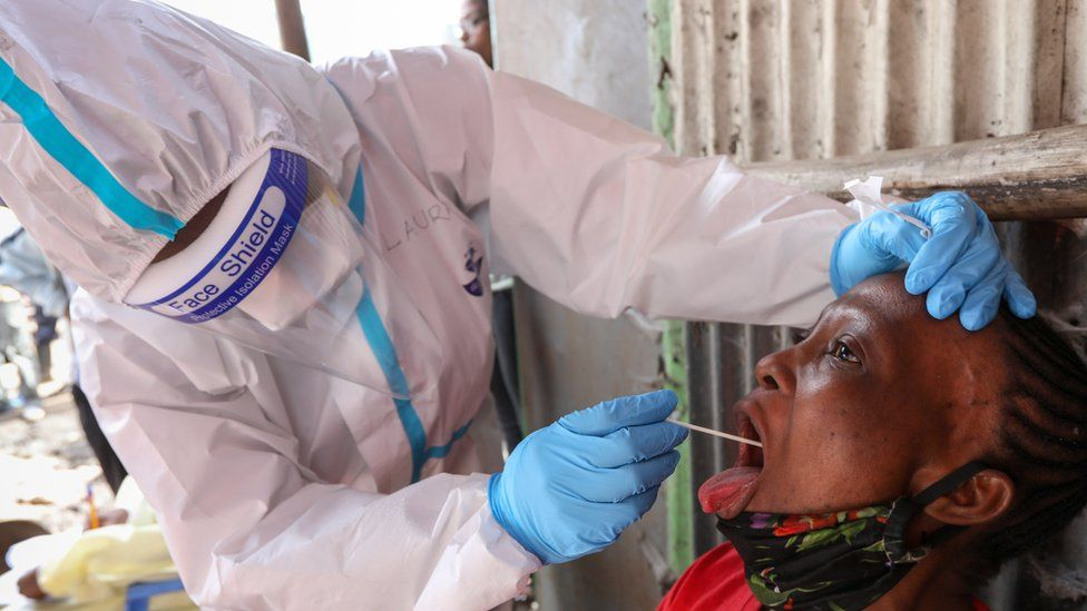 A Kenyan health worker in protective gear (L), uses a oral swab to collect a sample from a woman during a mass testing exercise for SARS-CoV-2 coronavirus